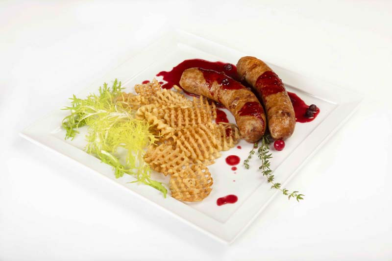 Roasted venison sausages with potato chips and  red bilberry sauce